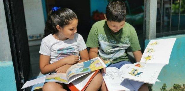 Dos niños con libros y dibujando.