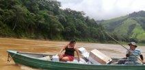 En un bote dos personas cruzan un río con los materiales donados.