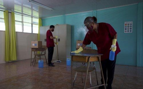 Fotografía de conserjes con mascarilla y guantes, desinfectando un aula