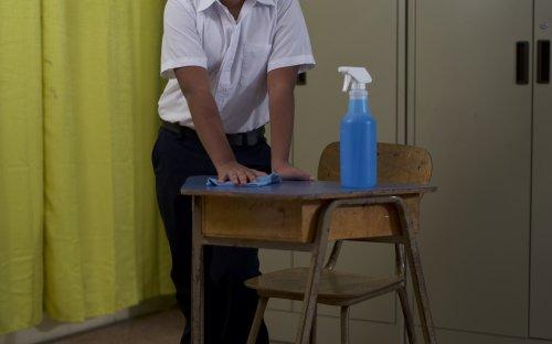 Estudiante limpiando un pupitre dentro de un aula