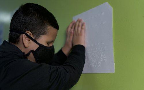 Fotografía de estudiante con discapacidad visual leyendo información en braille