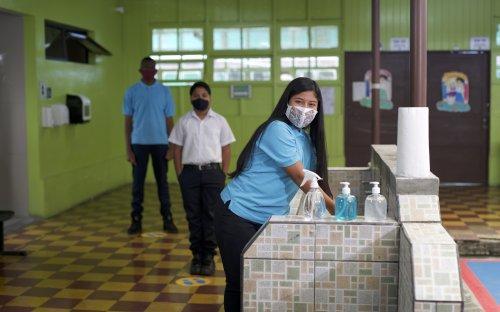 Tres estudiantes con mascarilla en el centro educativo haciendo fila