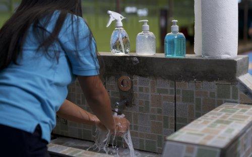 Estudiante lavándose las manos con agua y jabón