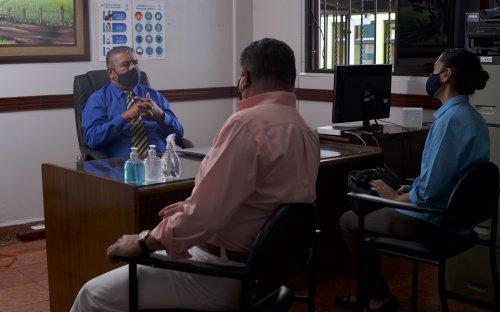 Familiares reunidos con el director en su oficina, distanciamiento y mascarillas