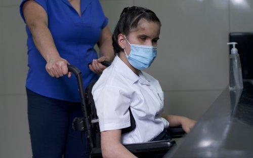 Estudiante en silla de ruedas cerca de lavado de manos