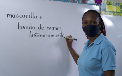 Docente con mascarilla escribiendo en una pizarra: mascarilla + lavado de manos
