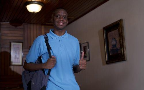 Estudiante de colegio en su casa, realizando una seña de aprobación