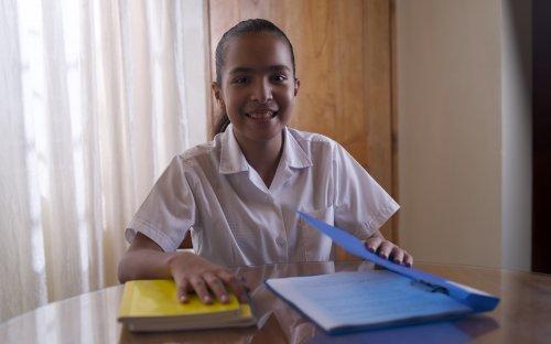 Estudiante de escuela en su casa, abriendo cuadernos en la mesa del comedor