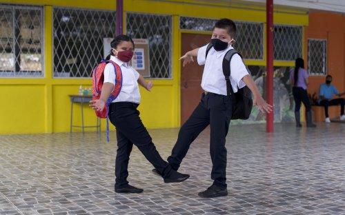 Dos estudiantes saludándose con el pie en el pasillo de un centro educativo