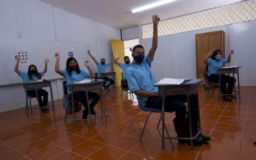 Varios estudiantes con mascarilla en un aula con las manos levantadas