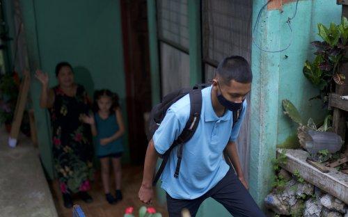 Estudiante con mascarilla saliendo de su casa, familia al fondo despidiéndose
