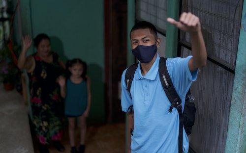 Estudiante con mascarilla saliendo de su casa. Su familia al fondo despidiéndose