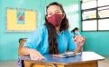 Estudiante con mascarilla en un aula, limpiando su pupitre