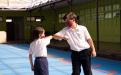 Estudiantes de primaria saludándose con el codo, ambos utilizan mascarilla