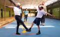 Estudiantes de primaria saludándose con el pie, ambos utilizan mascarilla